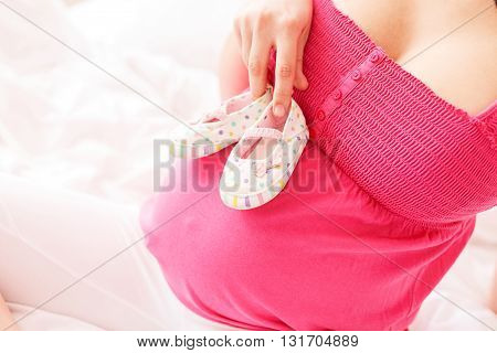 Close up of female hand holding baby shoes near her belly. Pregnant woman is sitting on bed
