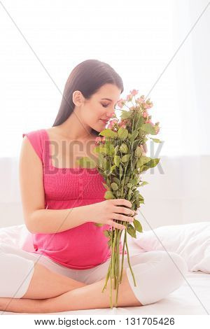 Pretty young pregnant woman is holding and smelling a bouquet of roses. She is sitting on bed and smiling. Her eyes are closed with enjoyment