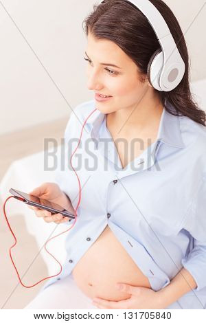Beautiful young pregnant woman is listening to music from headphones. She is sitting on bed and holding a mobile phone. The lady is touching belly and smiling