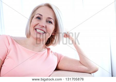 Active beautiful middle-aged woman smiling friendly and looking into the camera. Woman's face closeup.
