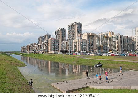 Saint - Petersburg, Russia - May 26, 2016: People stand near Matisov Canal. On the background is a new residential complex