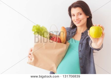 Pretty young expectant mother is going shopping. She is holding a package of healthy food and smiling. Lady is standing and showing an apple to camera. Isolated and copy space in left side