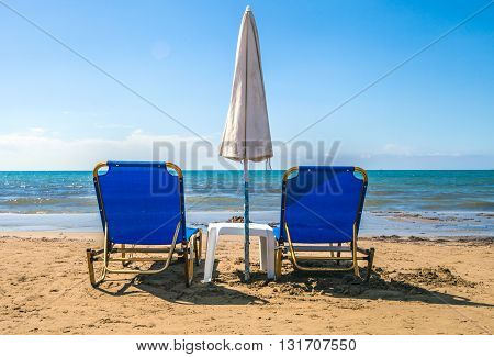 Empty Lounge Chairs With Sun Umbrella On Sandy Beach