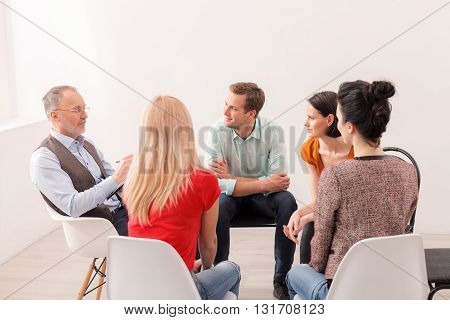 Experienced psychologist is consulting a group. He is sitting and explaining them something with seriousness. The man and women are listening to him attentively