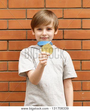 blond boy is happy gold medal - champion, winner