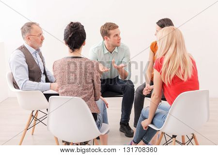 Desperate young man is asking advice in group and psychologist. He is sitting and gesturing with frustration