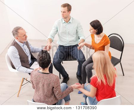 Professional mature psychotherapist is consulting the group. They are holding hands and listening to the man attentively