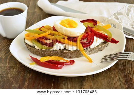 Sandwich with black bread cottage cheese peppers and boiled egg for breakfast