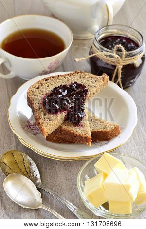 Wholegrain toast with blackcurrant jam and butter, vertical