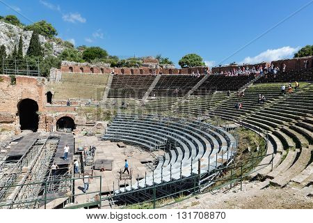 TAORMINA ITALY - MAY 17: Tourists visiting the ancient Greek theater of Taormina city while workers mounting a stage on May 17 2016 in Taormina at the island Sicily Italy