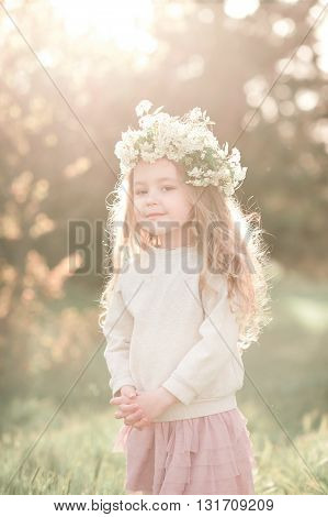 Cute baby girl 4-5 year old wearing stylish skirt and sweatshirt outdoors. Looking at camera. Childhood.