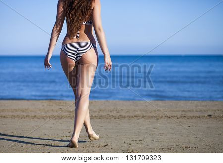 Woman In Bikini On Beach Goes To The Sea During Summer Vacation