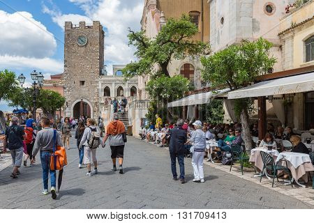 TAORMINA ITALY - MAY 21: Tourists walking along several restaurants at the main plaza of Taormina on May 21 2016 at the island Sicily Italy