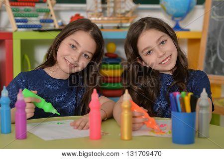 Cute schoolgirls twins on lesson of art at school