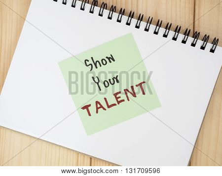 Handwriting Show Your Talent on blank notebook with wood background. (Business concept)
