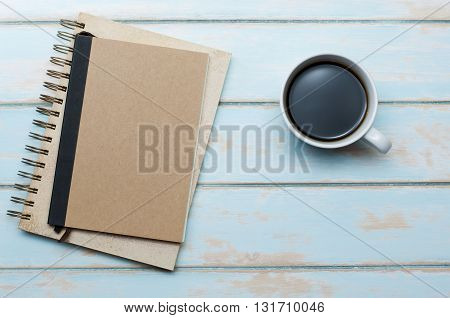 Black coffee with notebook and diary on blue sky wooden floor.