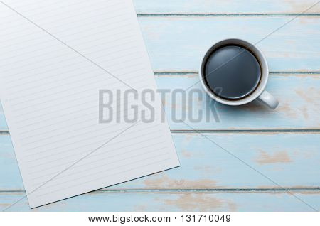 Top view coffee and notepaper on blue sky wooden floor.