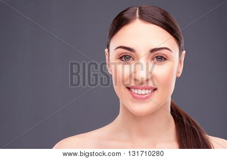 Portrait of beautiful young woman standing with naked shoulders. She is looking at camera and smiling. Isolated and copy space in left side