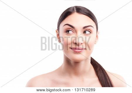 Portrait of beautiful girl looking aside with curiosity. She is standing and gently smiling. Isolated and copy space in left side