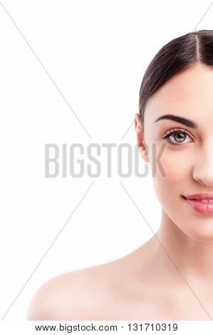 Close up of half of female face. Beautiful young woman is standing with naked smooth shoulder. She is looking at camera and smiling. Isolated