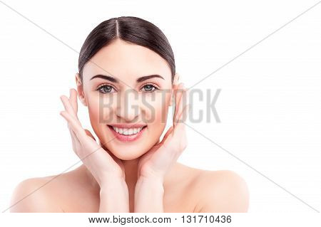 Portrait of beautiful young woman raising hands to perfect face. She is looking at camera and smiling with satisfaction. Lady is standing with naked shoulders. Isolated and copy space in right side