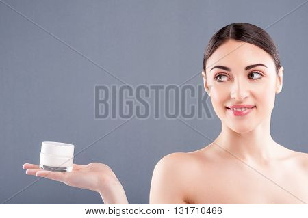 Portrait of beautiful young woman holding a cream jar for her skin. She is looking at it with interest and smiling. The lady is standing with naked shoulders. Isolated on grey background