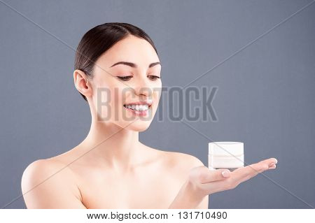 This is my favorite cosmetic product. Portrait of attractive young woman holding a can of cream. She is looking at it and smiling. Isolated