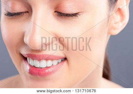 Close up of female beautiful face. Happy girl is smiling. Her eyes are closed with pleasure