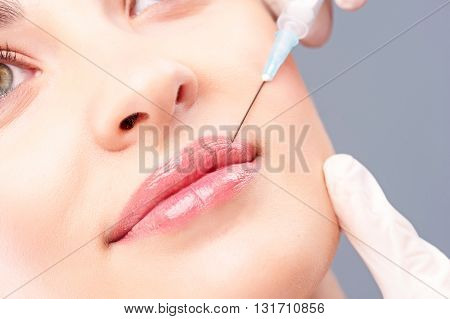 Close up of hand of doctor injecting botox into female lips