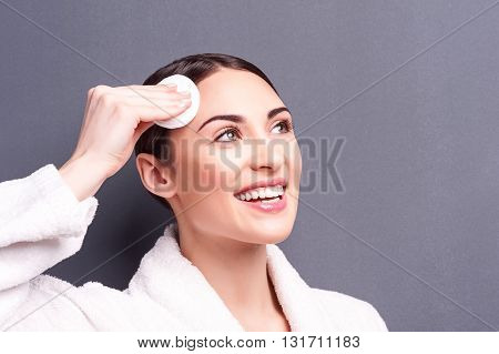 Portrait of pretty young woman treating her skin with enjoyment. She is touching her forehead with soft sponge. The lady is standing in bathrobe and smiling. Isolated and copy space in right side