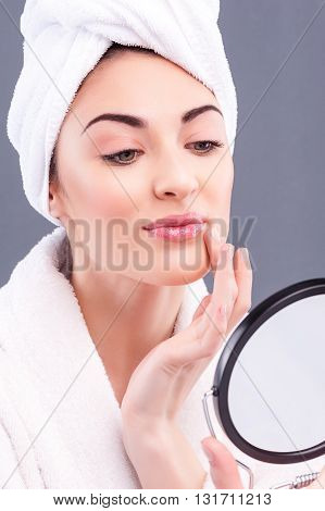 Portrait of attractive young girl looking at mirror with concentration. She is touching her facial skin. The lady is standing in bathrobe wrapped head with towel. Isolated