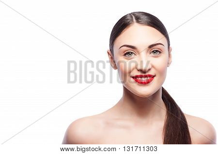 Portrait of beautiful girl standing and smiling. Her shoulders are bared. Isolated and copy space in left side