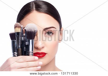 Portrait of attractive young woman holding and covering her eye with a set of make-up brush. She is standing and looking at camera confidently. Isolated and copy space in right side