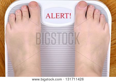 Barefoot person standing on the weight scale. The scale shows ALERT!