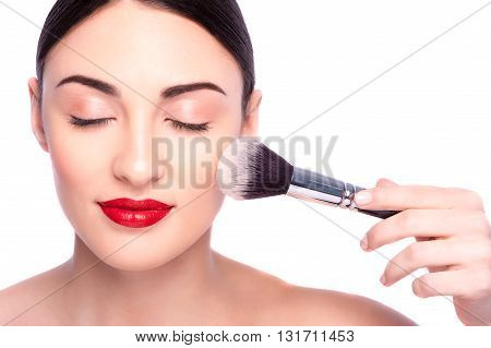 Portrait of pretty girl doing make-up. Her eyes are closed with pleasure. Female hand of beautician is holding a brush and applying powder on her face. Isolated