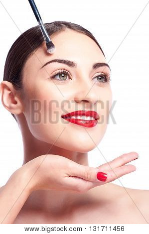 Close up of hand of beautician applying eyeshadows under female eyebrow. Attractive young woman is standing and smiling. Isolated