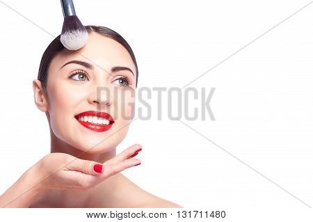 Pretty female model is getting facial make-up. Beautician is touching powder brush to her forehead. The lady is standing and smiling. Isolated and copy space in right side