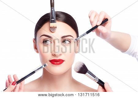 Close up of hands of professional beauticians doing make-up for young model. They are holding brush and applying powder on female face. Attractive girl is looking sideways with joy. Isolated