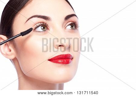 Portrait of beautiful young woman applying mascara on her eyelash. She is looking forward with confidence. Isolated and copy space in right side