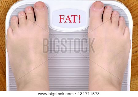 Barefoot person standing on the weight scale. The scale shows FAT!