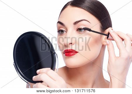 Pretty girl is paining her eyelash with mascara. She is standing and holding a mirror. The lady is looking at her reflection with concentration. Isolated