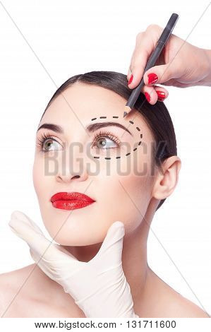 Portrait of beautiful girl doing facial make-up. Hand of beautician is drawing her eyebrow with a pencil. The lady is calm and relaxed. There is imaginary line over her eye