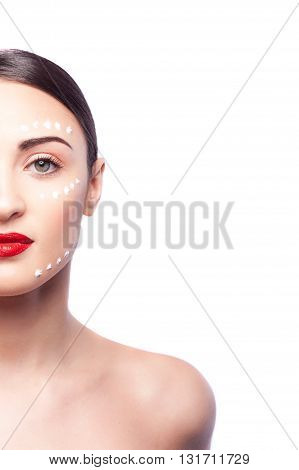 Close up portrait of half of female face with dots of cream. Young woman is standing and looking at camera with confidence. Isolated and copy space in right side