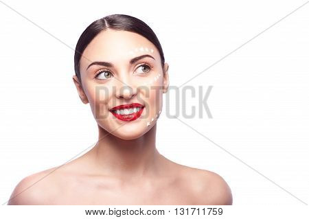 Portrait of healthy girl standing and smiling happily. There are dots of cream on her forehead, cheek and chin. Isolated and copy space in right side