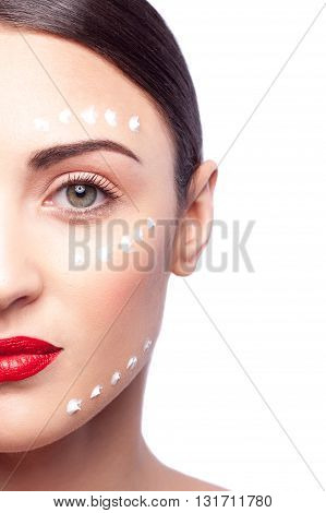 Close up of half of female face. Young woman is standing and looking forward confidently. Dots of cream are applied on her skin. Isolated