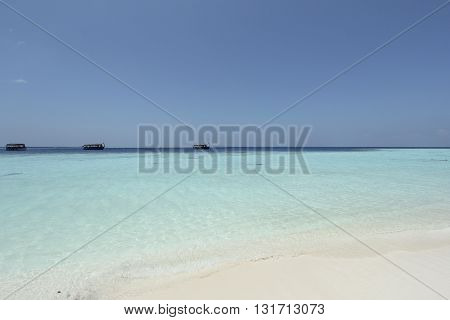 whute beach and turquise sea with boars in the Maldives