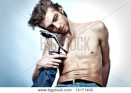 Shot of a handsome man holding woman's leg in elegant shoes.