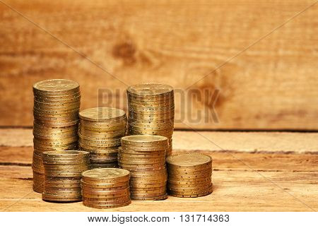 Piles of old coins on the wooden table