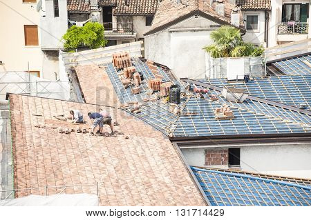 Udine , Italy - May 2 2016 :  construction site. Masons to work on the roof for laying tiles