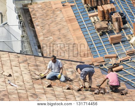 Udine , Italy - May 26 2016 : Construction site. Masons to work on the roof for laying tiles